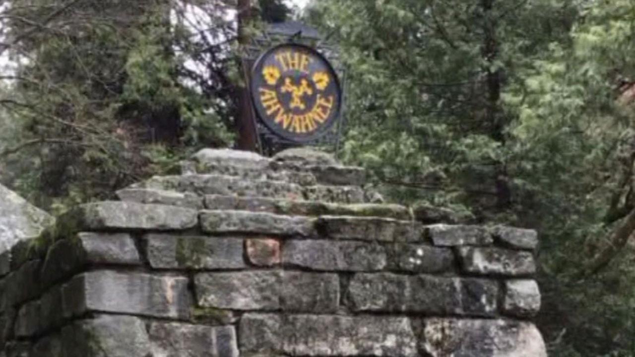 Sign for Ahwahnee Hotel at stone gatehouse at Yosemite National Park.
