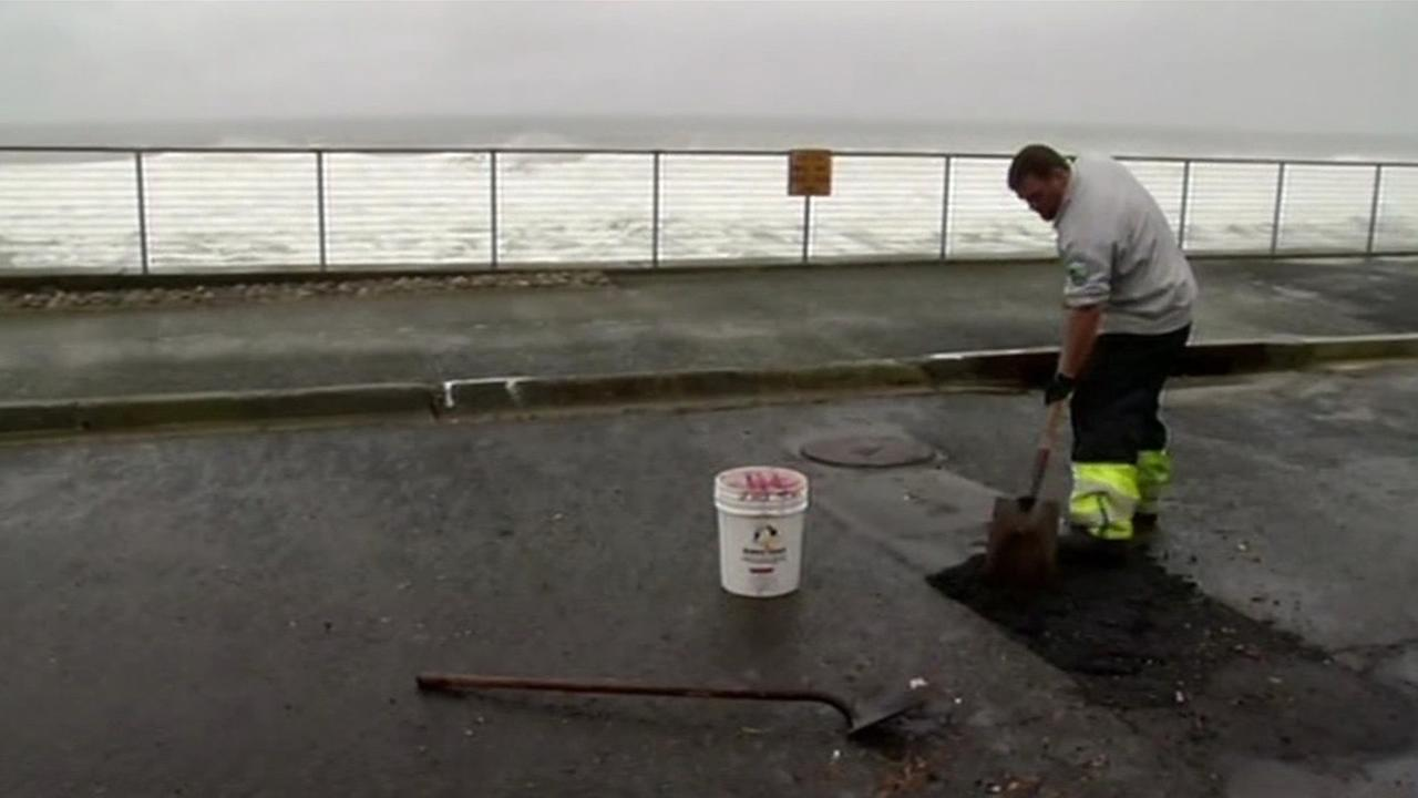 Crews work to fill potholes in Pacifica, Calif., on Friday, March 4, 2016. KGO-TV