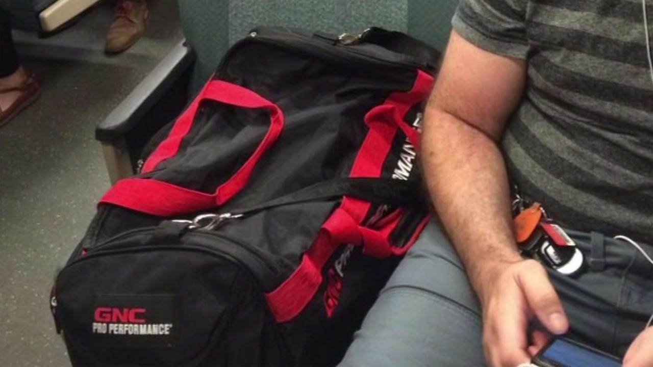 This image shows a BART rider who is taking up two seats with his bag.