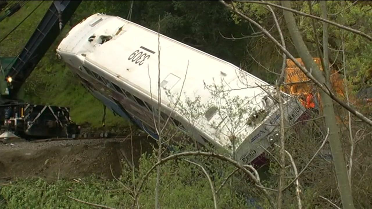 Crews work to remove a derailed ACE train car from an embankment on Tuesday, March 8, 2016 in Sunol, Calif. KGO-TV