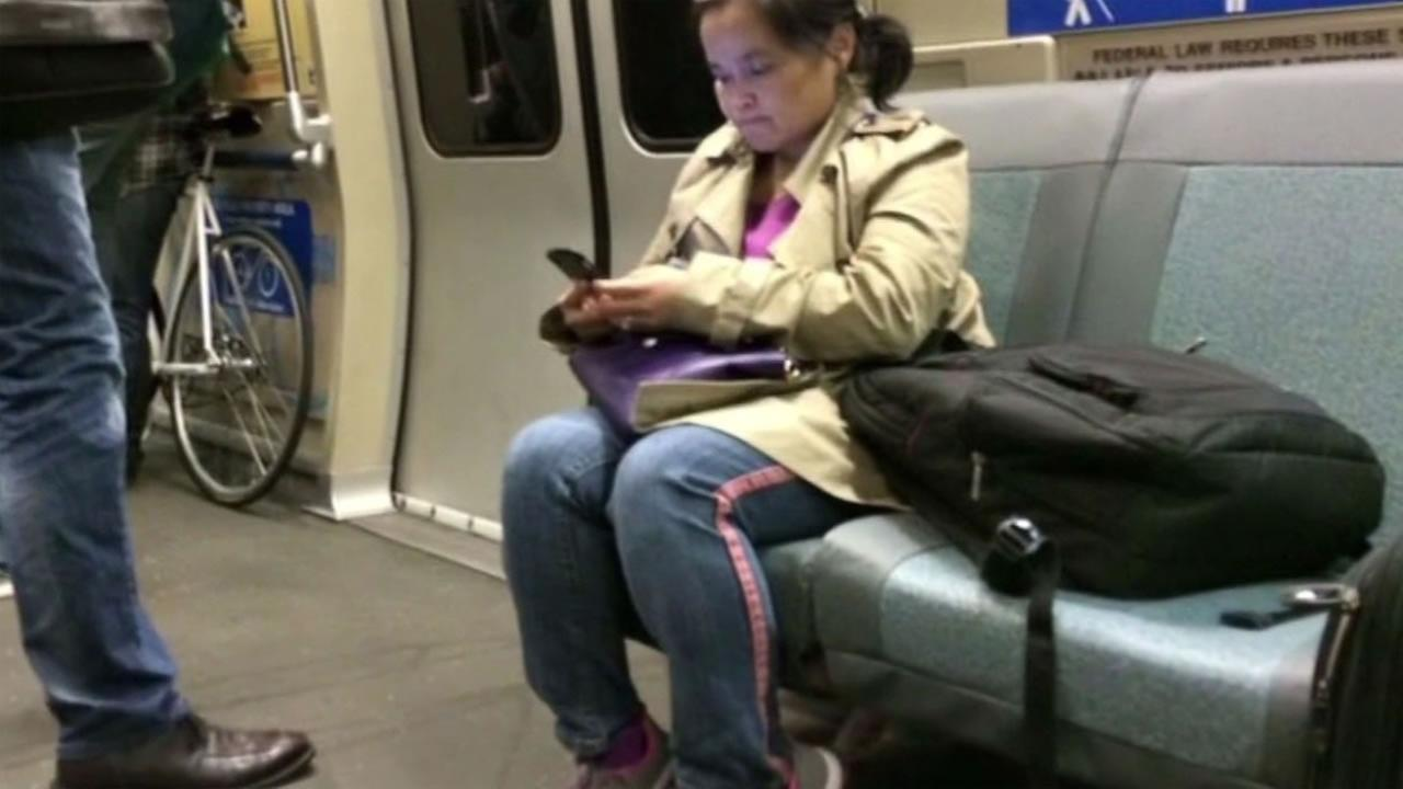 A BART passenger takes up two seats on a train.