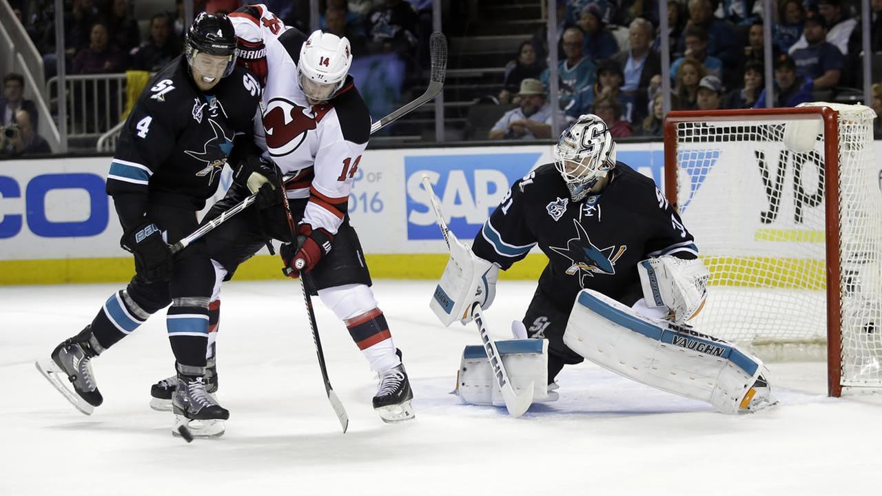 Sharks Brenden Dillon defends Devils Adam Henrique as goalie Martin Jones watches during an NHL hockey game Thursday, March 10, 2016, in San Jose, Calif. (AP Photo)