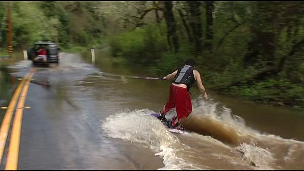A man wakeboards down a flooded road in Sonoma County, Calif. on Friday, March 11, 2016.KGO-TV