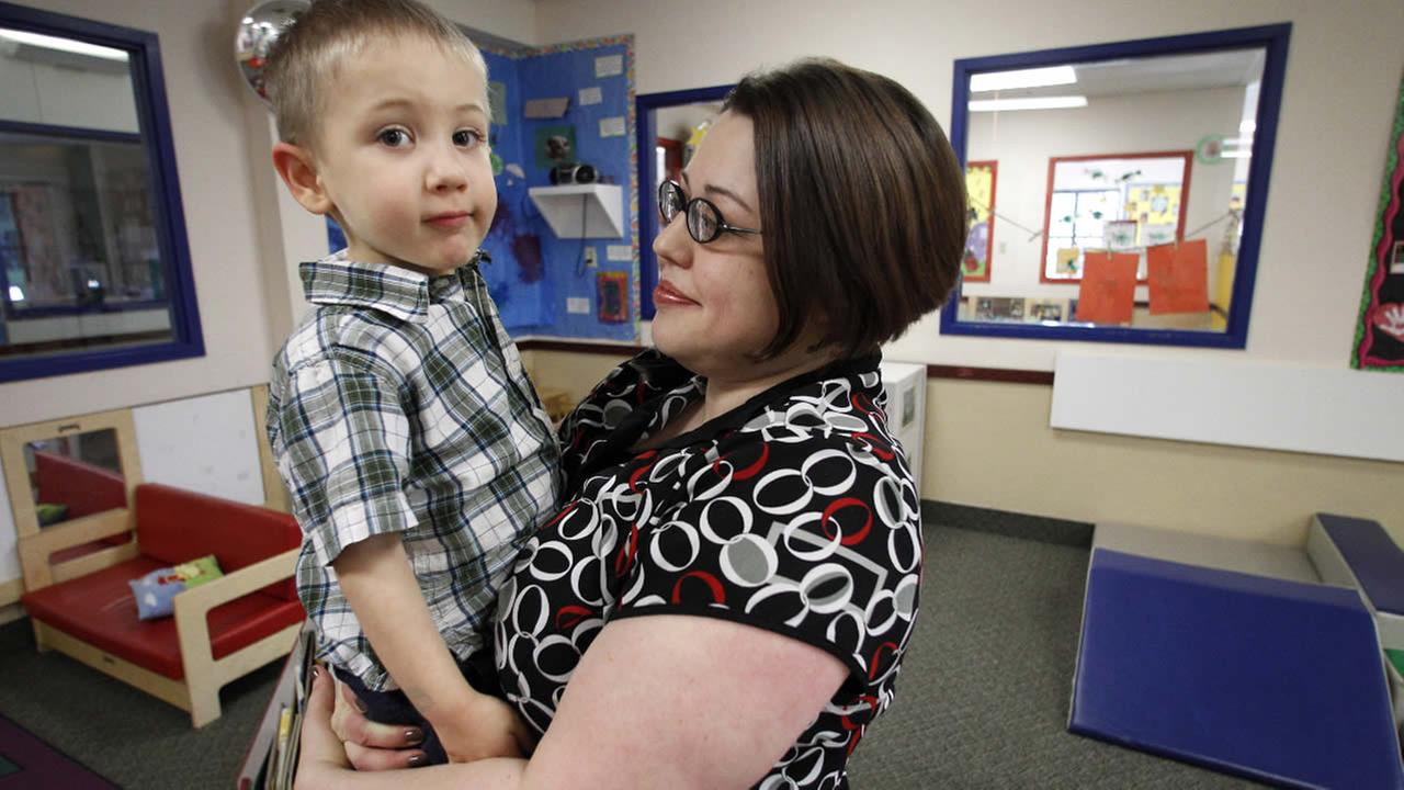 FILE: Kelly Andrus holds her son Bradley in his classroom at Childrens Choice Learning Centers Inc., in Lewisville, Texas.