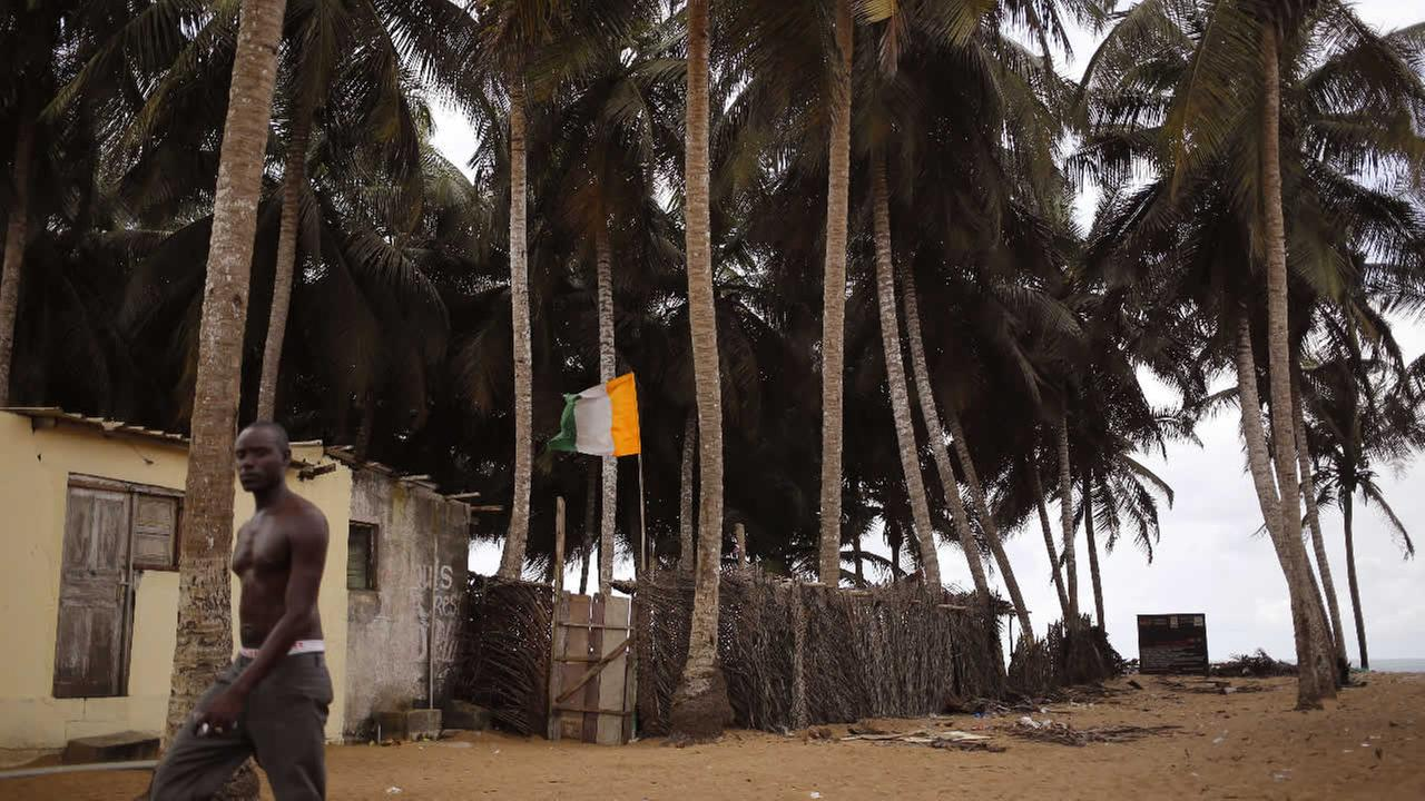 FILE: A man passes a home stead, with an Ivory Coast national flag seen at a fishing village renowned as a tourist hot spot visited by French and other tourist yearly in Grand Bassam, Ivory Coast.