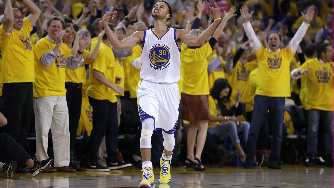 In this May 13, 2015, file photo, fans cheer as Warriors Curry reacts after scoring during Game 5 in the NBA playoff basketball series against the Grizzlies. (AP Photo/Ben Margot)