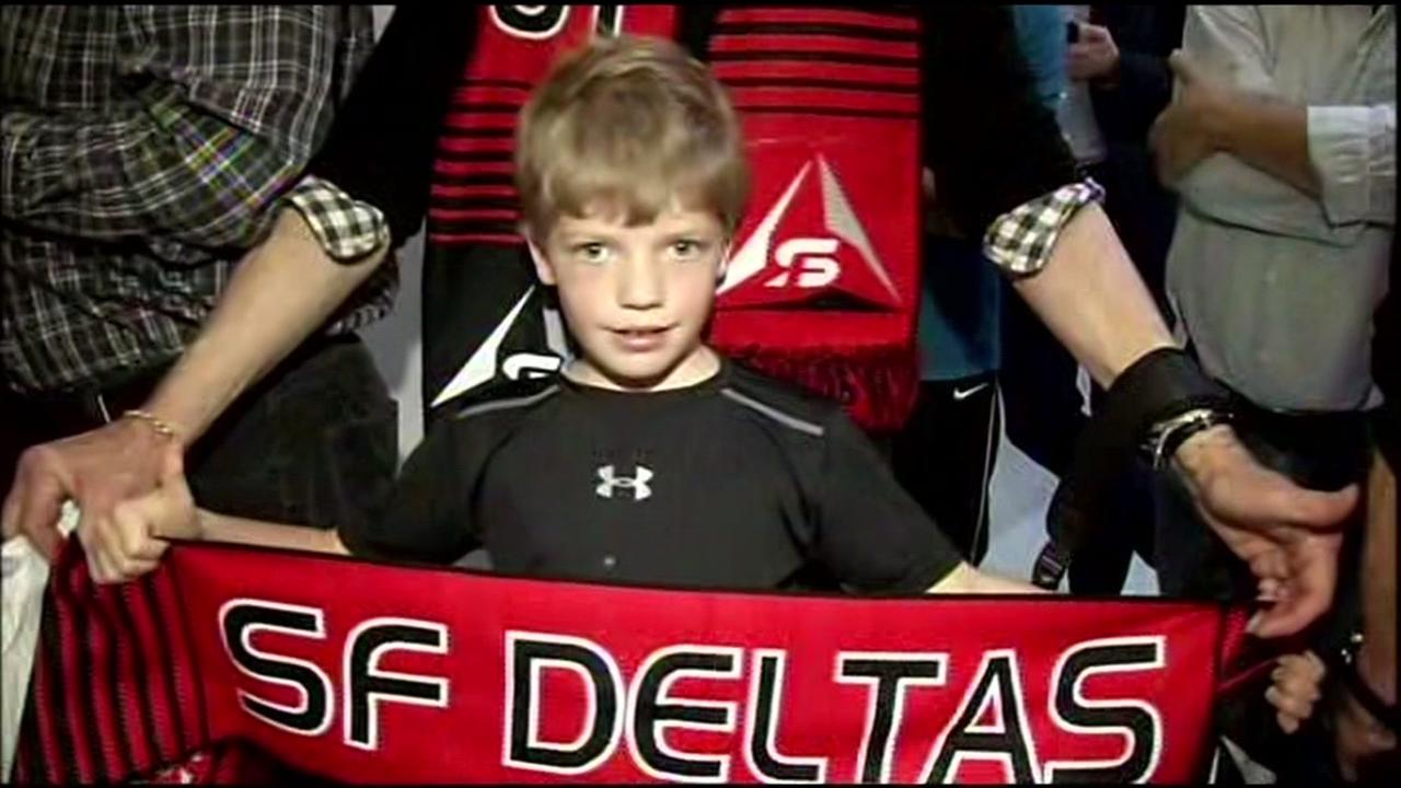 A boy holds up a San Francisco Deltas scarf on Thursday, March 17, 2016.