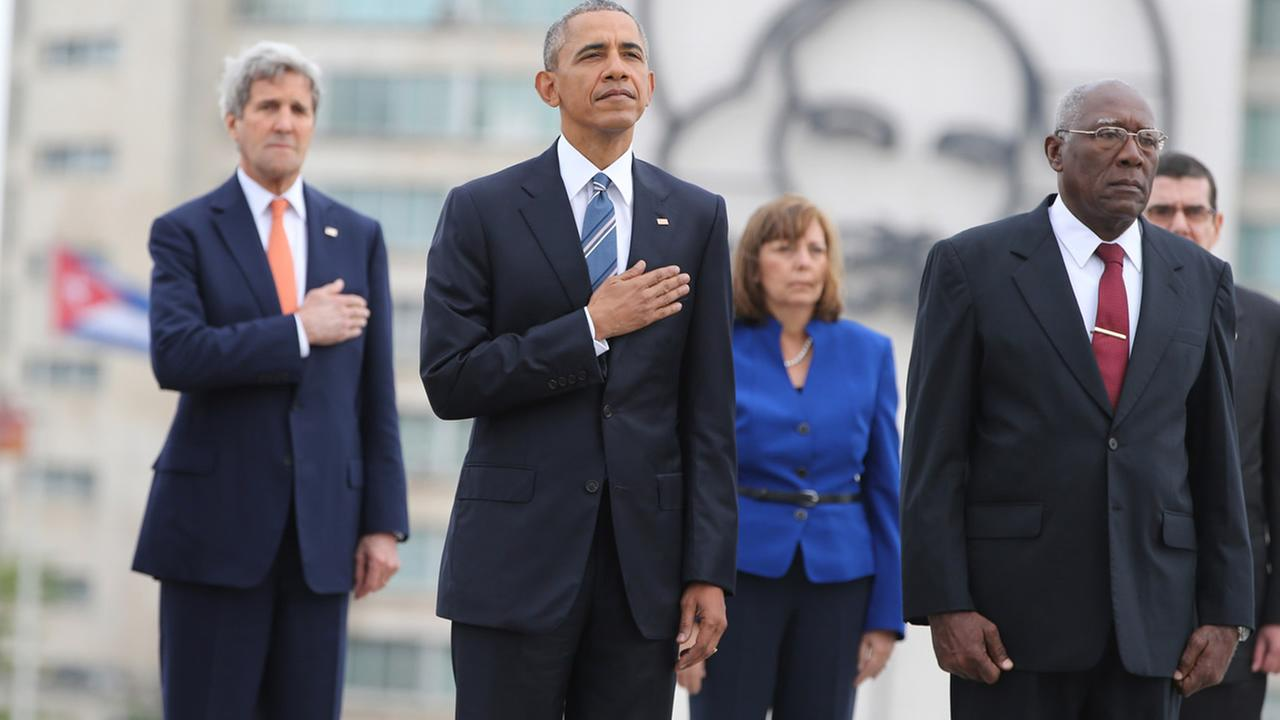 U.S. President Barack Obama and Secretary of State John Kerry listen to the U.S. national anthem during a ceremony at Revolution Square in Havana, Cuba, Monday, March 21, 2016.