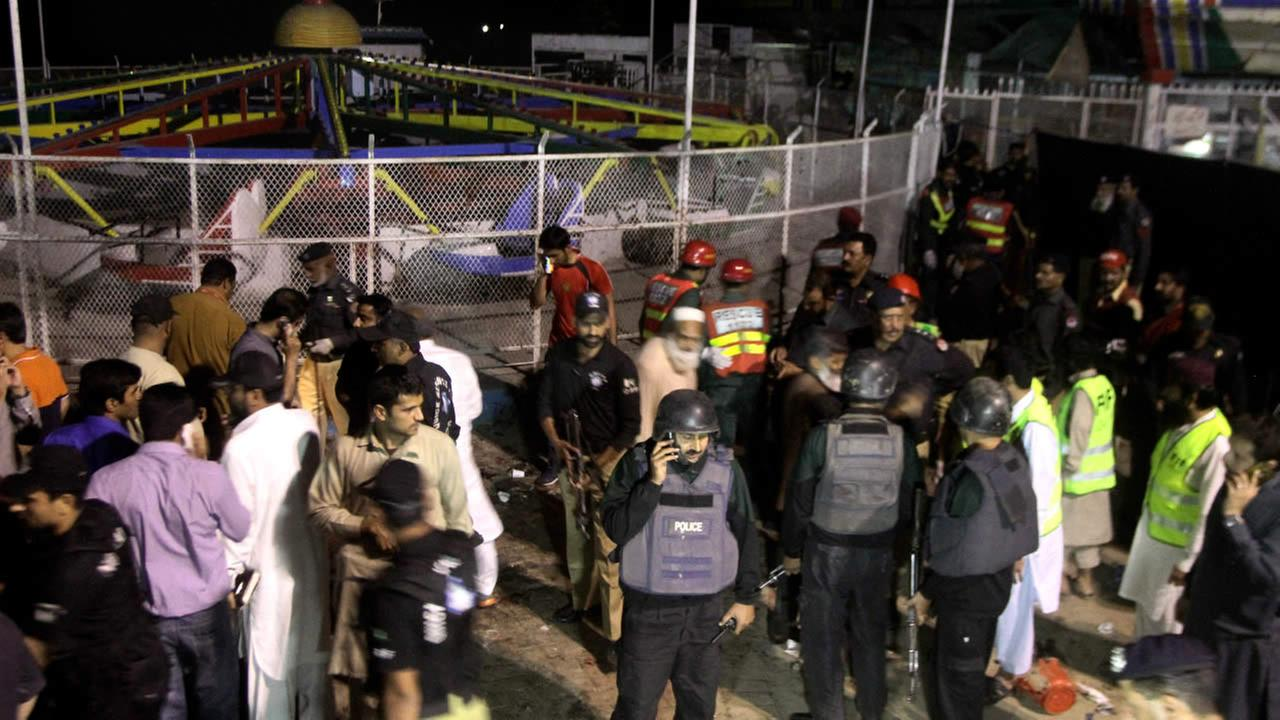 Pakistani police officers and rescue workers gather at the site of bomb explosion in a park in Lahore, Pakistan, Sunday, March, 27, 2016.