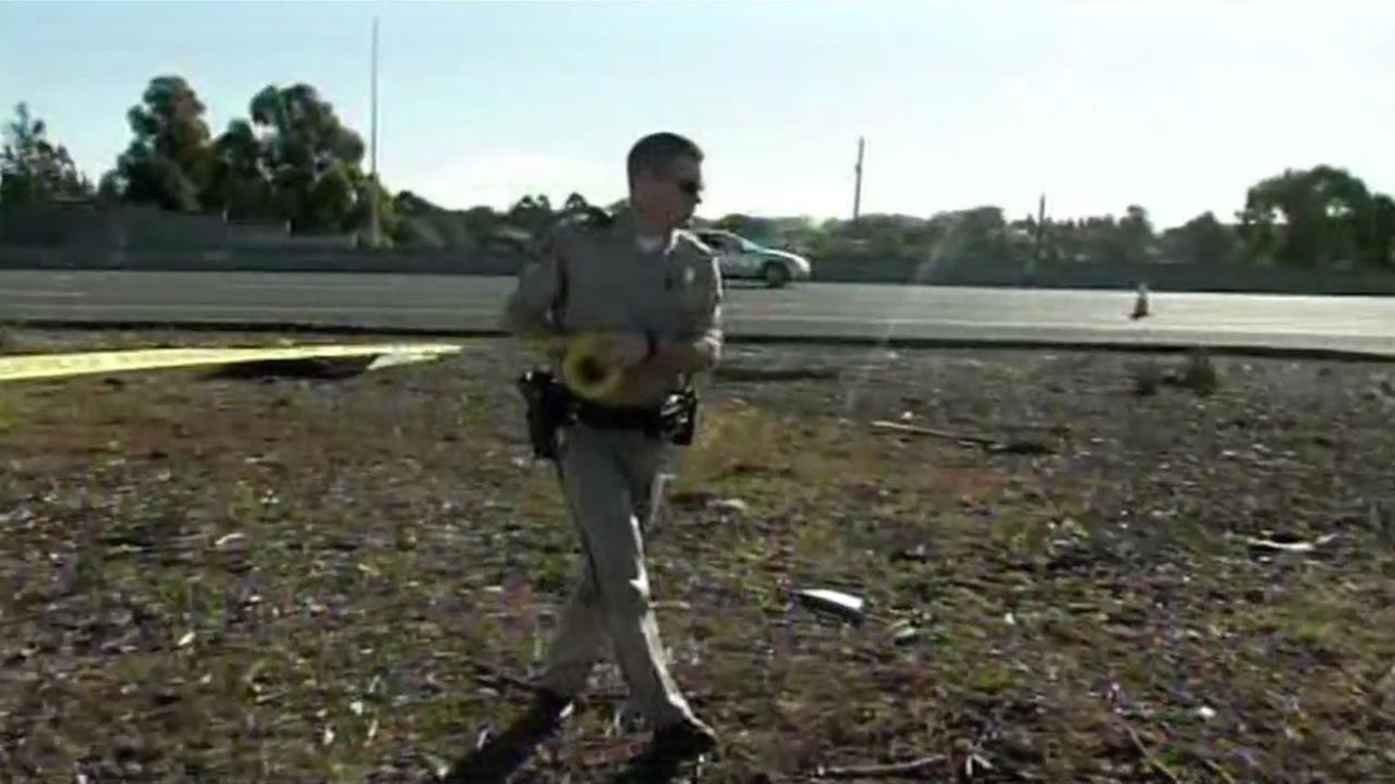 A CHP officer puts crime tape up at the scene of a fatal shooting on westbound I-80 in February.