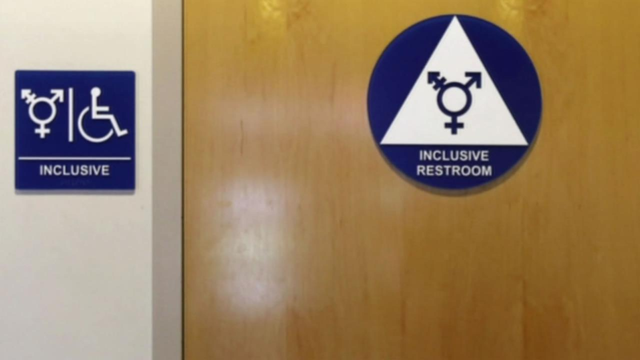 A gender-inclusive restroom sign is pictured.