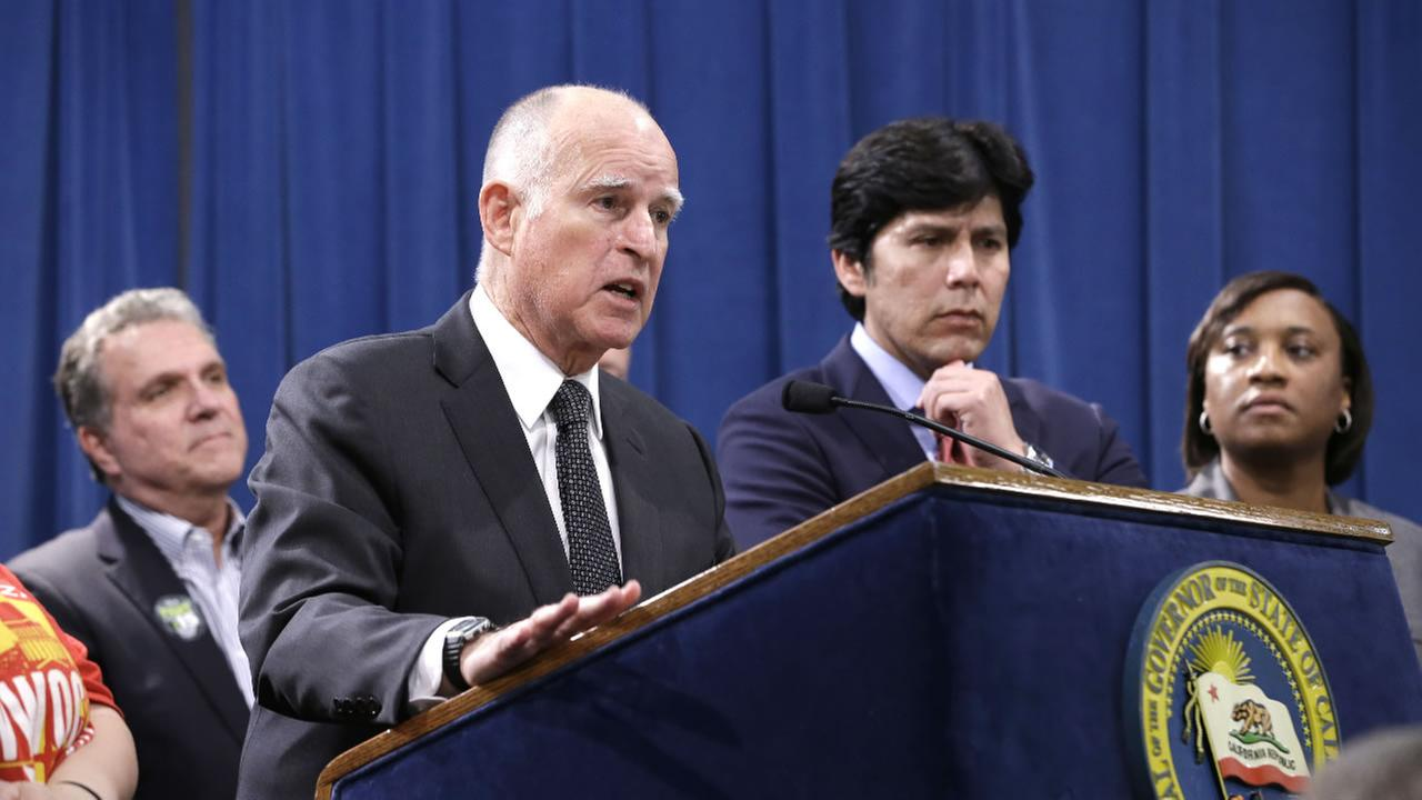 Accompanied by labor leaders and Senate President Pro Tem Kevin de Leon, second from right,  Gov. Jerry Brown discusses proposed legislation to increase the states minimum wage to $15 per hour in Sacramento, Calif. Monday March 28, 2016.
