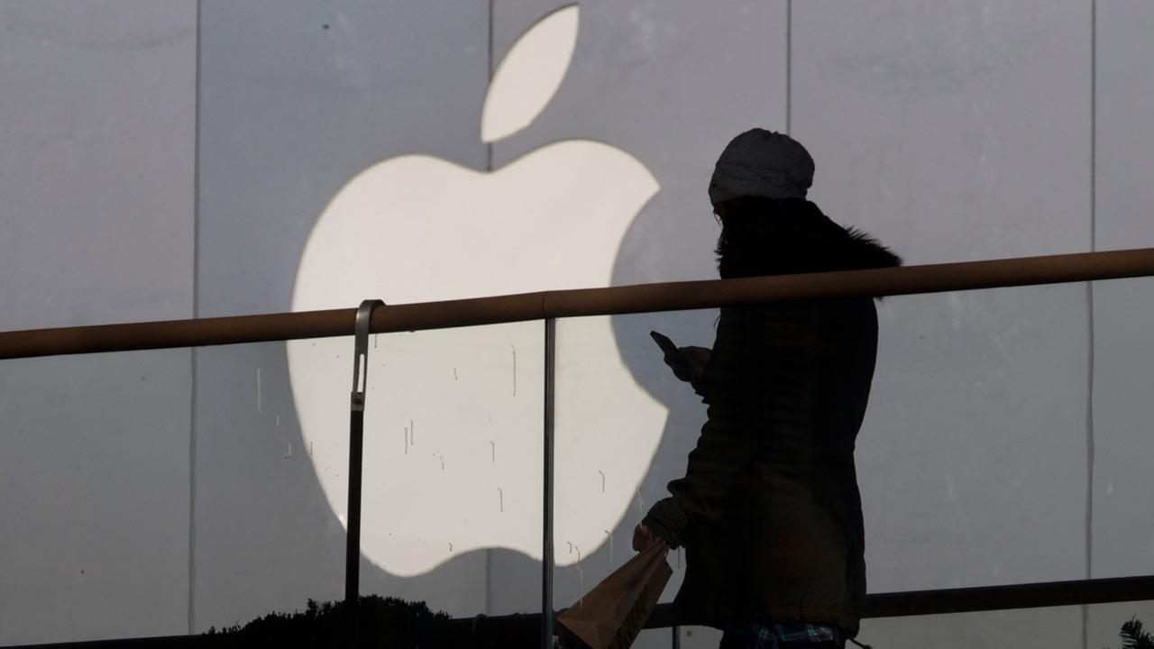 FILE - In this Dec. 23, 2013, file photo, a woman using a phone walks past Apples logo near its retail outlet in Beijing.