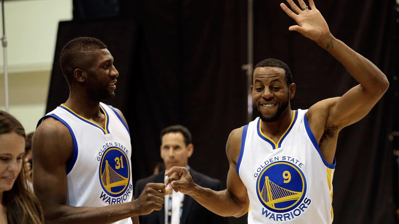 Golden State Warriors Festus Ezeli, left, and Andre Iguodala (9) greet one another during an NBA basketball media day Monday, Sept. 28, 2015, in Oakland, Calif.