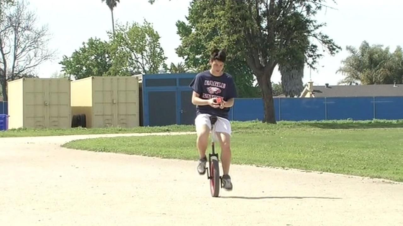 This image shows 16-year-old Owen Farmer at American High School in Fremont, Calif. April 2, 2016 riding a unicycle while solving a Rubiks Cubes.