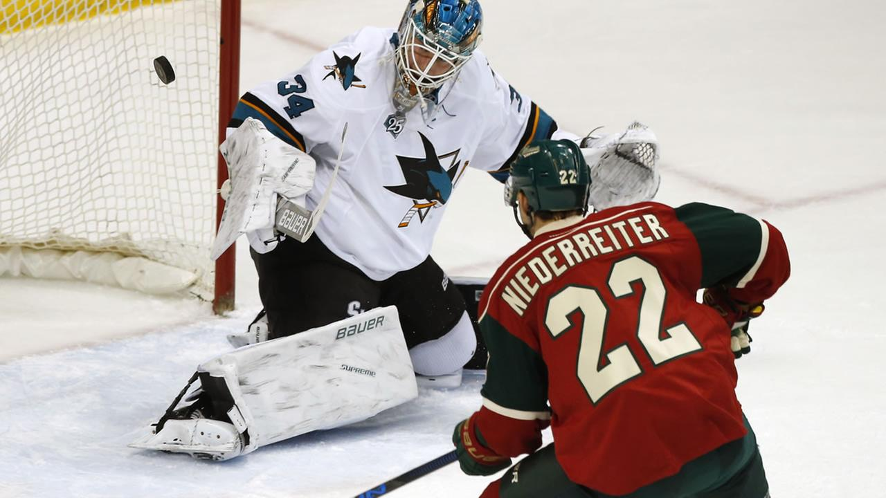 Wilds Nino Niederreiter of Switzerland, positions himself for a rebound as Sharks James Reimer stops a shot during an NHL hockey game Tuesday, April 5, 2016, in Minn. (AP Photo)