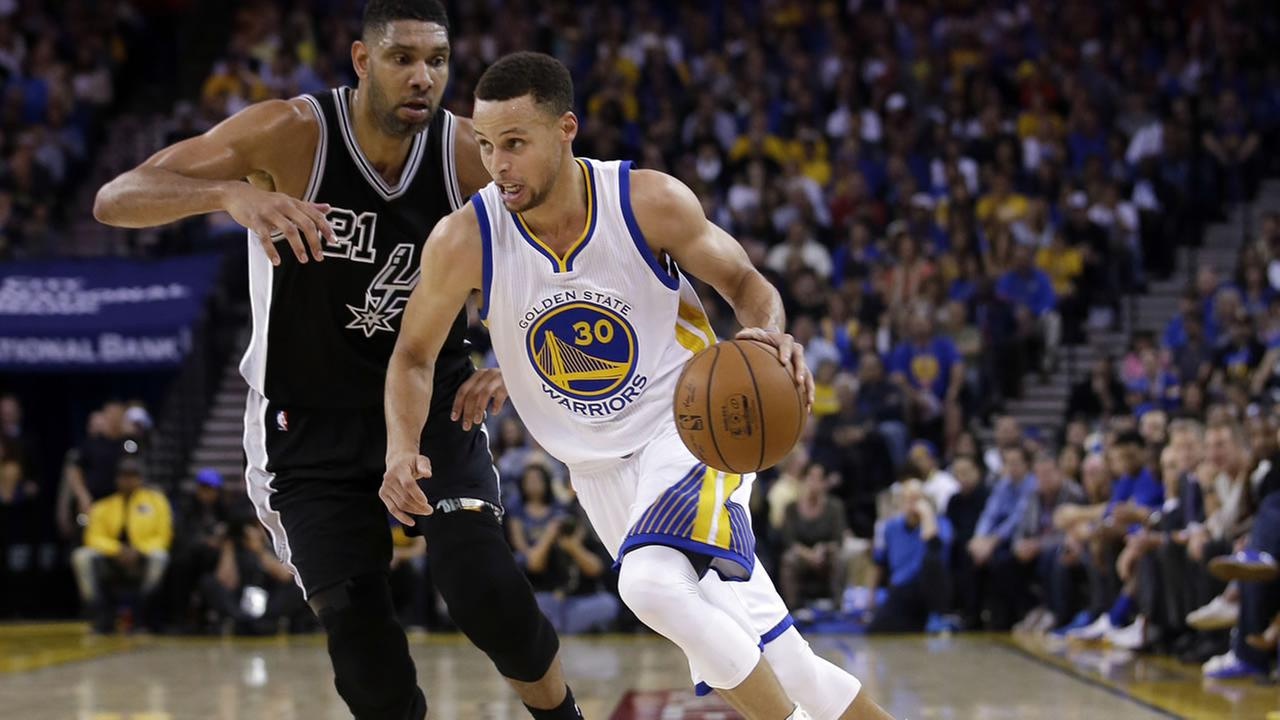 Warriors Stephen Curry (30) dribbles past San Antonio Spurs Tim Duncan during an NBA basketball game Thursday, April 7, 2016, in Oakland, Calif. (AP Photo/Marcio Jose Sanchez)