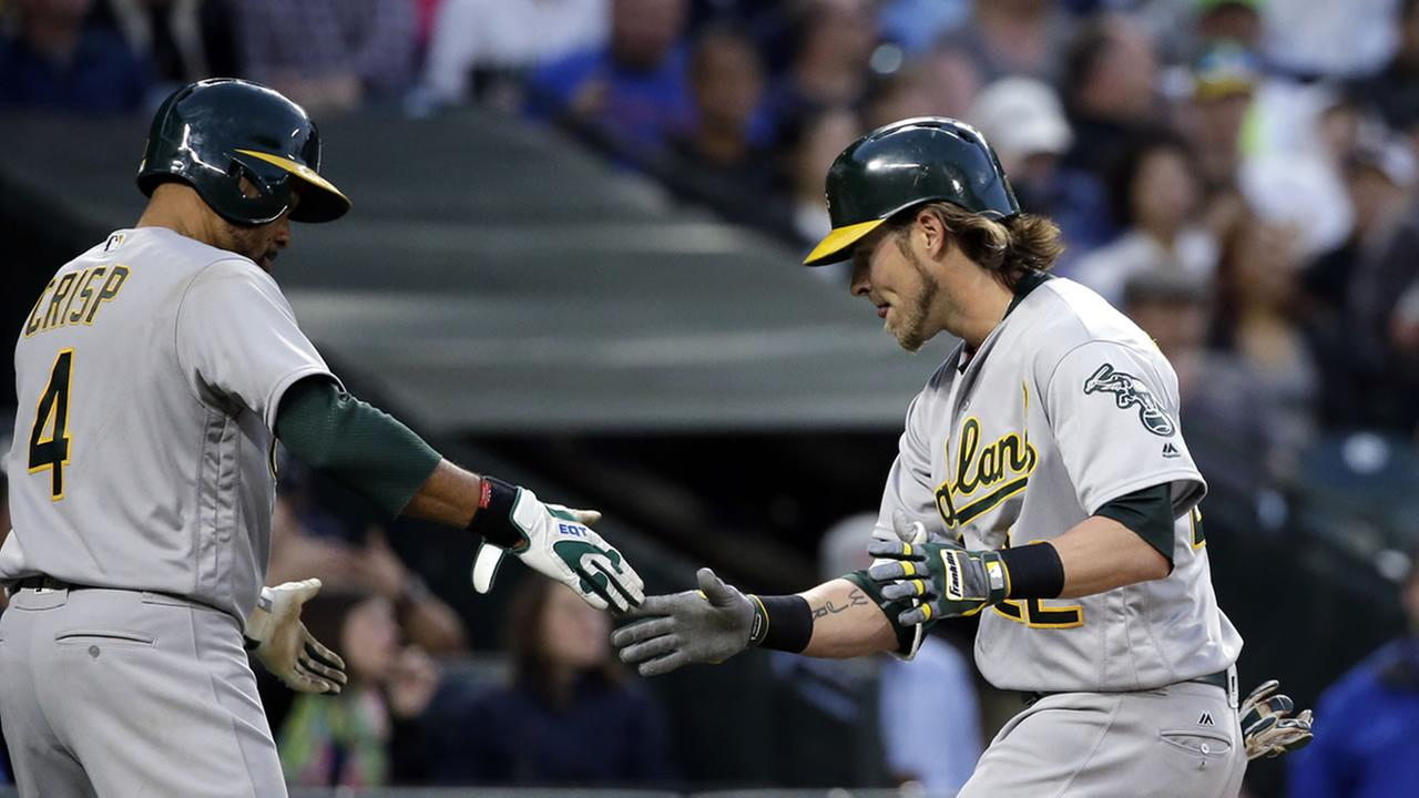 Oakland Athletics Josh Reddick, right, is congratulated by Coco Crisp (4) on his two-run home run against the Seattle Mariners in the fifth inning April, 9, 2016.