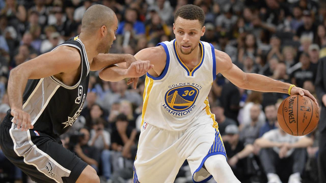 Warriors Stephen Curry (30) drives around Spurs Tony Parker, of France, during an NBA basketball game, Sunday, April 10, 2016, in San Antonio. (AP Photo/Darren Abate)
