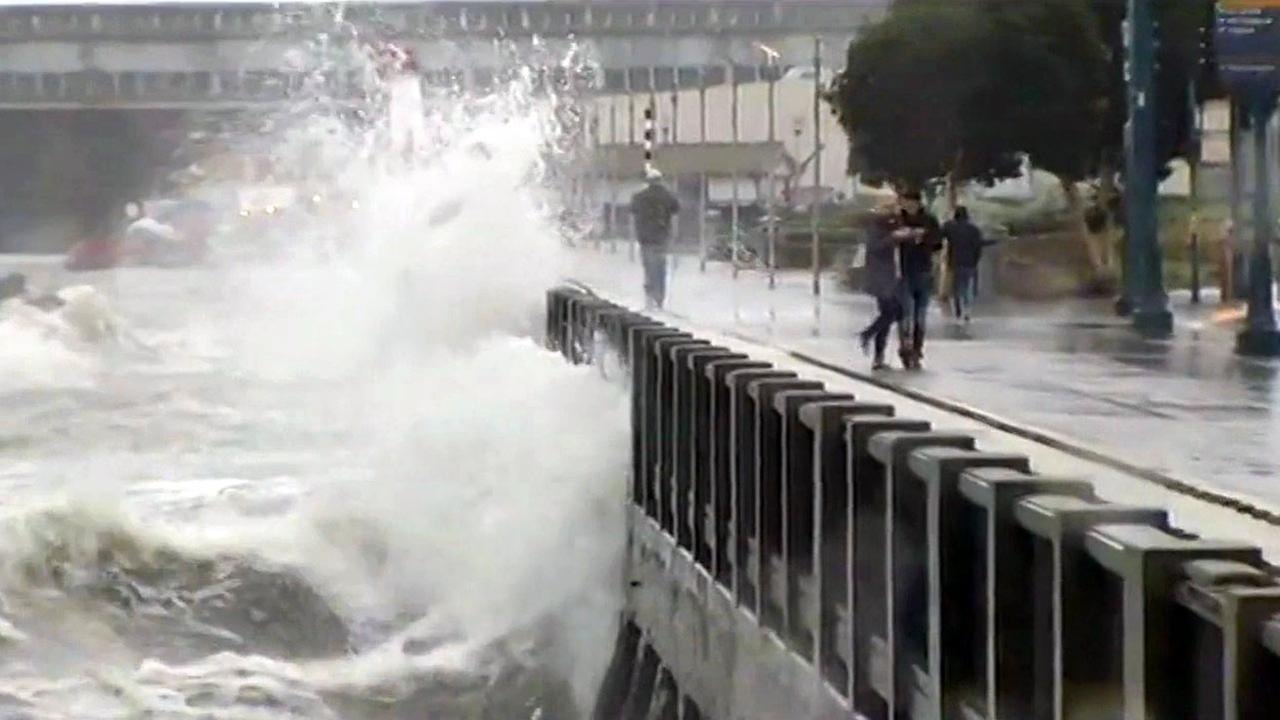 FILE -- Waves splash over Embarcadero seawall in San Francisco.