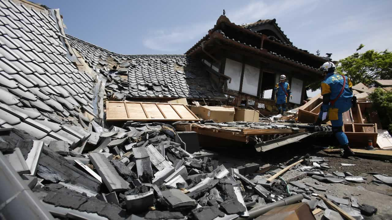 Police rescue team members search through damaged houses to check possibility of trapped people in Mashiki, Kumamoto prefecture, southern Japan, Friday, April 15, 2016.