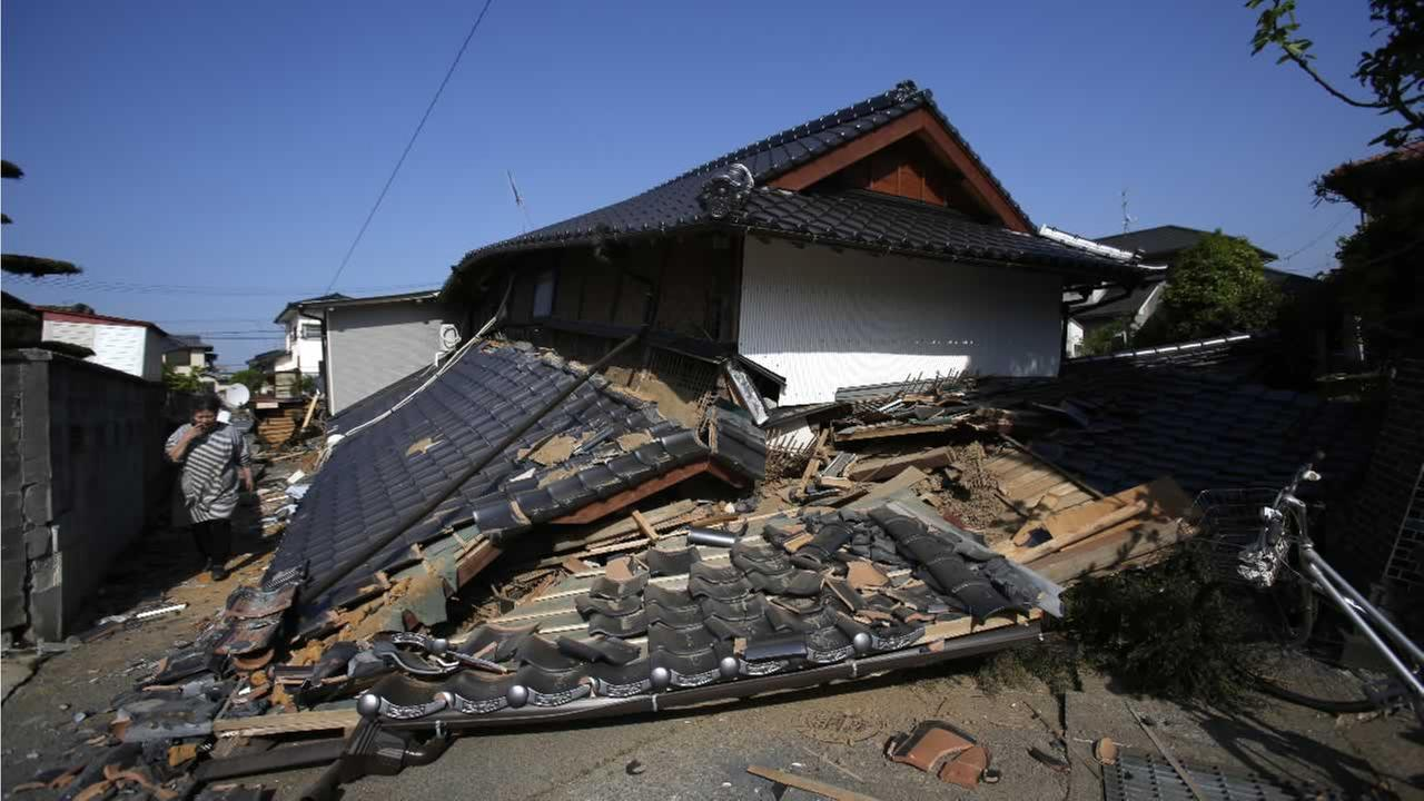 A resident walks by a collapsed house in Mashiki, Kumamoto prefecture, southern Japan, Friday, April 15, 2016.AP Photo/Koji Ueda