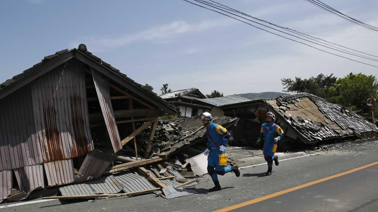 Police officers run in front of collapsed houses in Mashiki, Kumamoto prefecture, southern Japan, Friday, April 15, 2016.AP Photo/Koji Ueda