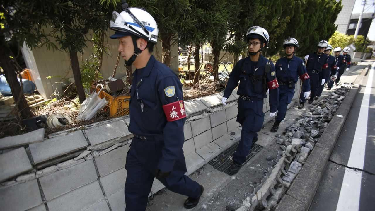 Police officers walk through debris during their search for people possibly trapped in their home in Mashiki, Kumamoto prefecture, southern Japan, Friday, April 15, 2016.AP Photo/Koji Ueda