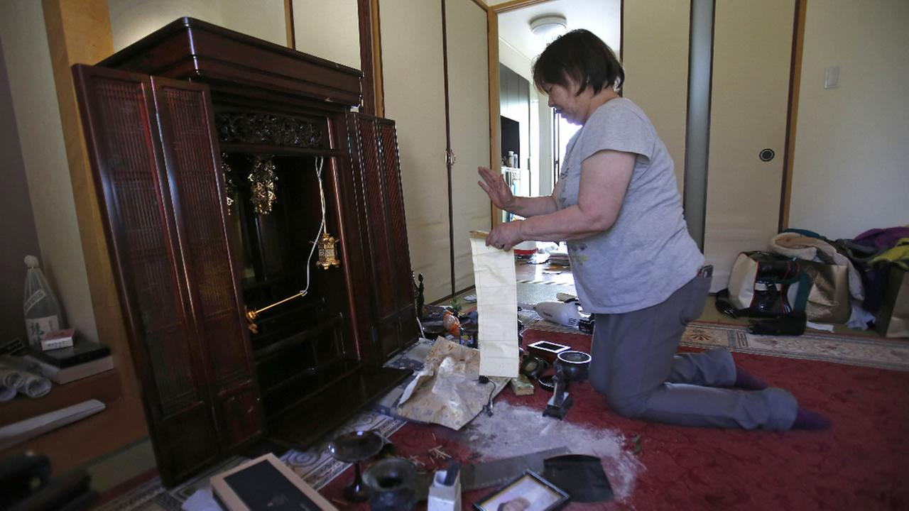 A resident cleans her mother?s Buddhist altar, which was collapsed during a magnitude-6.5 earthquake in Mashiki, Kumamoto prefecture, southern Japan, Friday, April 15, 2016.AP Photo/Koji Ueda