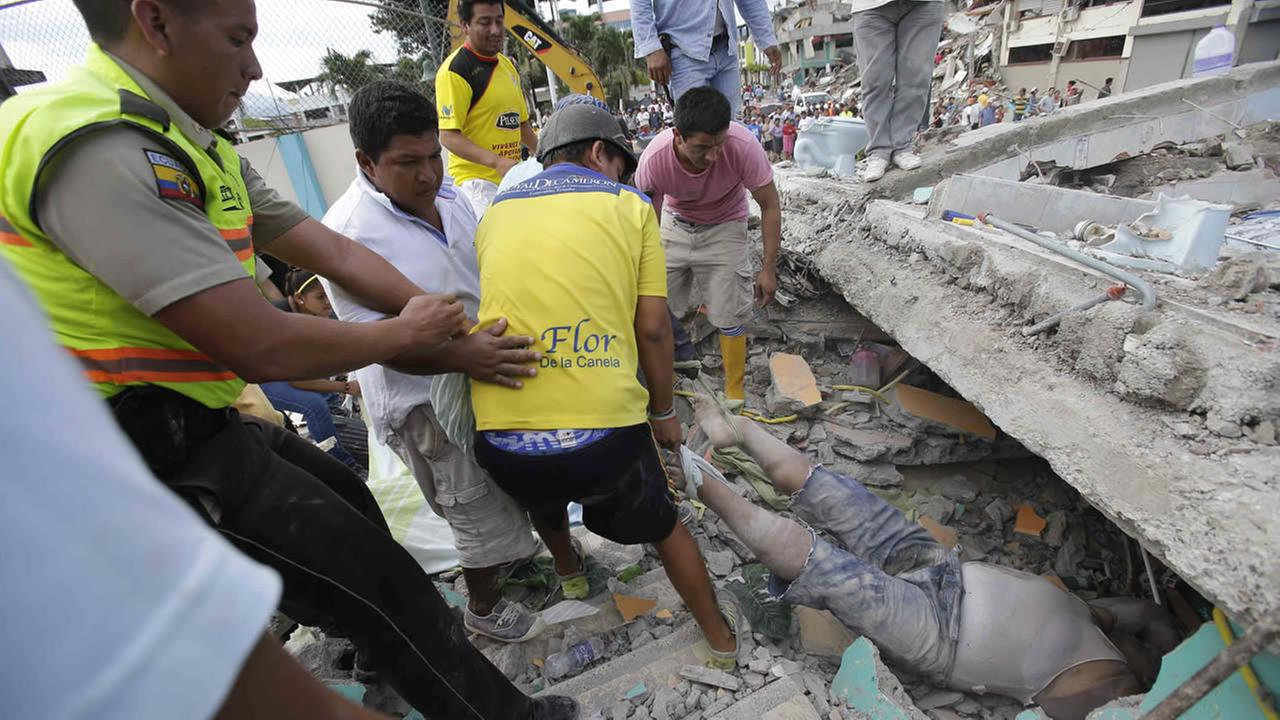 Volunteers rescue a body from a destroyed house after a massive in earthquake in Pedernales, Ecuador, Sunday, April 17, 2016. (AP Photo/Dolores Ochoa)