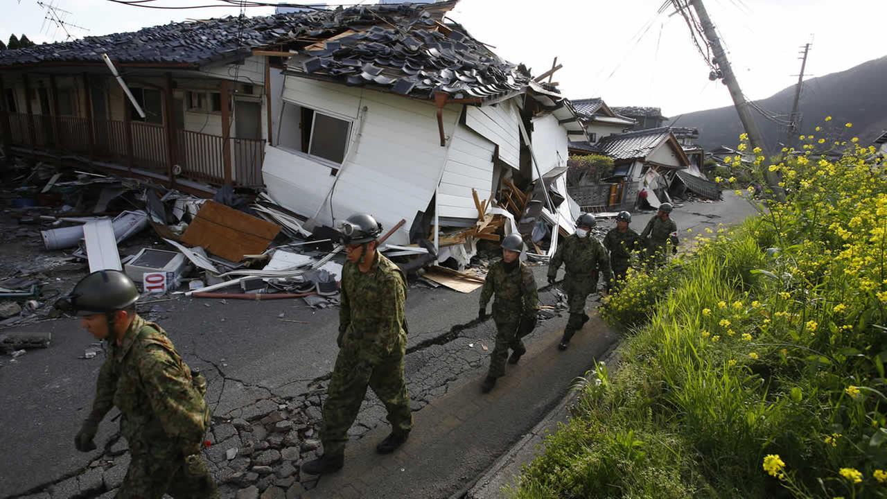 Japan Self-Defense Forces members survey the damage area caused by earthquakes in Minamiaso, Kumamoto prefecture, Japan, Sunday, April 17, 2016. (AP Photo/Shizuo Kambayashi)