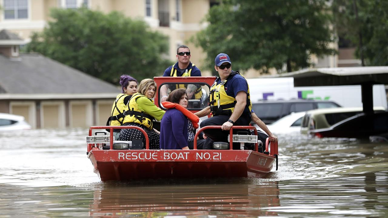 Residents are evacuated from their flooded apartment complex Tuesday, April 19, 2016, in Houston. (AP Photo/David J. Phillip)
