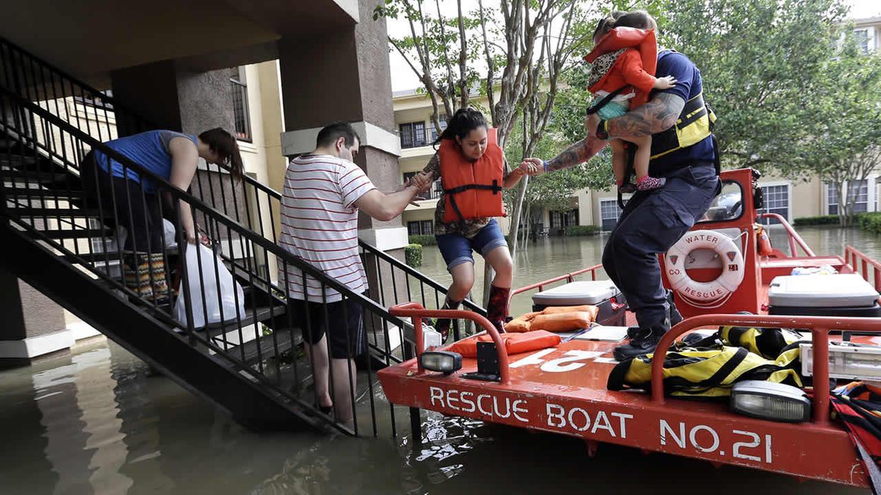 Residents are evacuated from their flooded apartment complex Tuesday, April 19, 2016, in Houston. (AP Photo/David J. Phillip)AP Photo/David J. Phillip