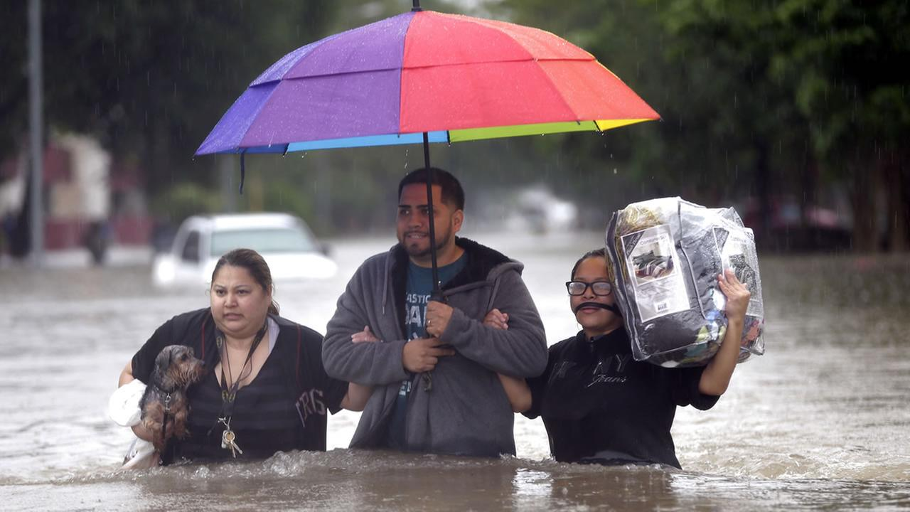 Felix Yanez, center, helps Lucy Olvio, right, and Judy wade through floodwaters as they evacuate from their flooded apartment complex Monday, April 18, 2016, in Houston. (AP Photo/David J. Phillip)AP Photo/David J. Phillip