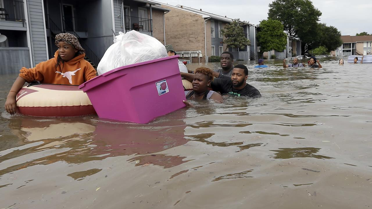 Residents wade through floodwaters as they evacuate their apartment complex Monday, April 18, 2016, in Houston. (AP Photo/David J. Phillip)AP Photo/David J. Phillip