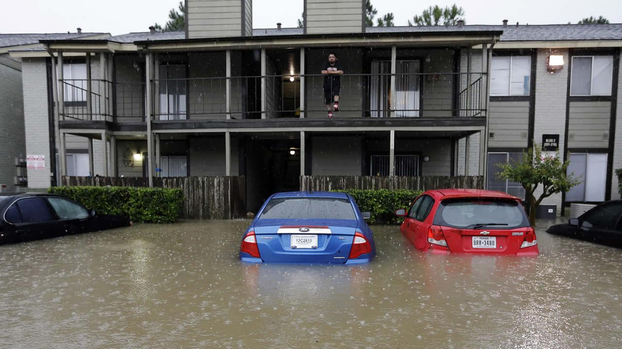A resident looks out from the second floor as floodwaters surround his apartment complex Monday, April 18, 2016, in Houston.AP Photo/David J. Phillip