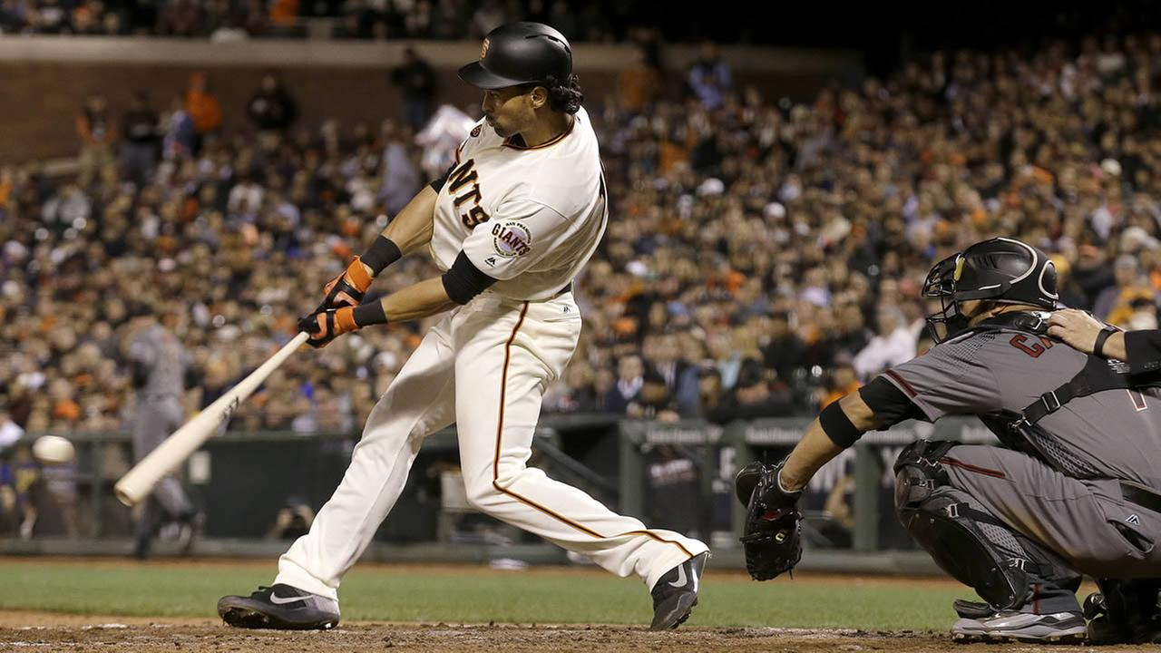 Giants Angel Pagan hits a two-run double in front of Diamondbacks Welington Castillo during a game in San Francisco, Monday, April 18, 2016. (AP Photo/Jeff Chiu)