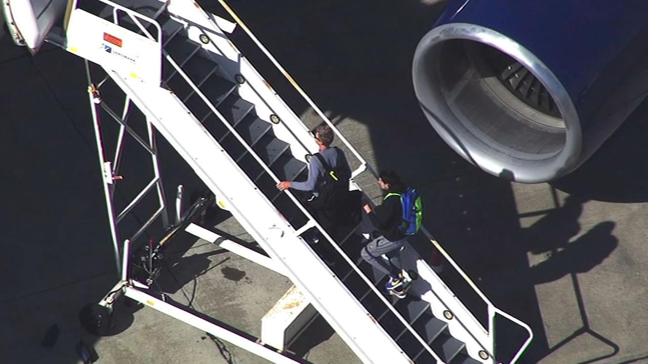 This image shows Warrior coach Steve Kerr and another Warriors player boarding a plane bound for Houston at the Oakland Airport April 20, 2016.