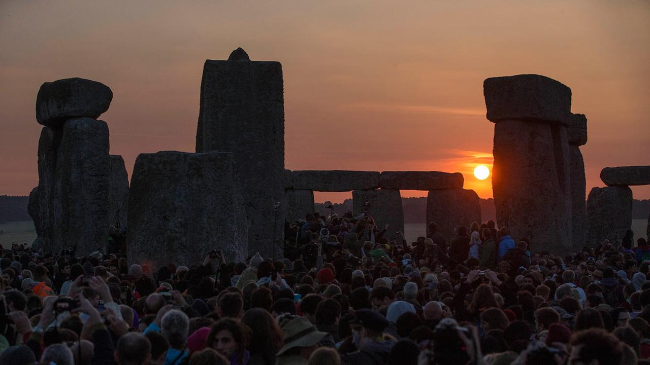 The sun rises as thousands of revelers gathered at the ancient stone circle Stonehenge, near Salisbury, England, to celebrate the summer solstice, the longest day of the year, Saturday, June 21, 2014. (AP Photo/Sang Tan)