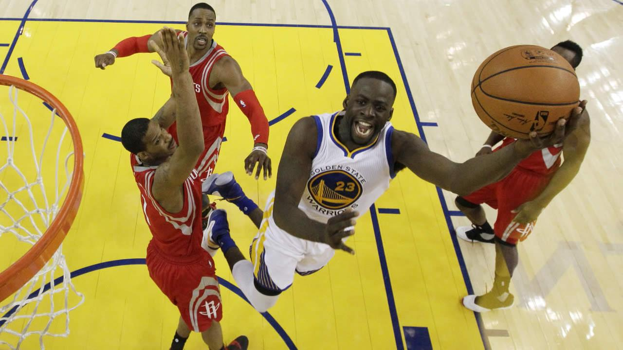 Warriors Draymond Green drives past the Houston Rockets players in Game 5 of a first-round NBA basketball playoff series Wednesday, April 27, 2016, in Oakland, Calif.