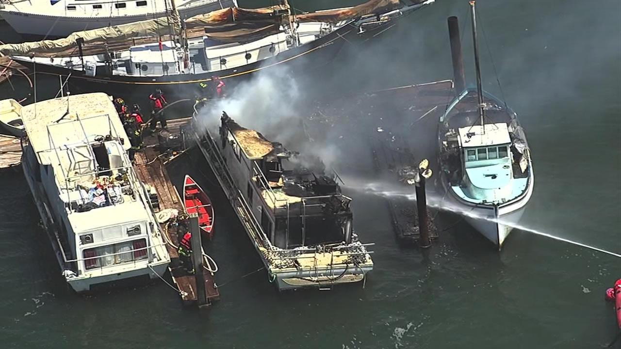 Fire crews worked to put out a fire on a boat docked in the Oakland Estuary near Fifth Avenue and Embarcadero on Monday, May 2, 2016.