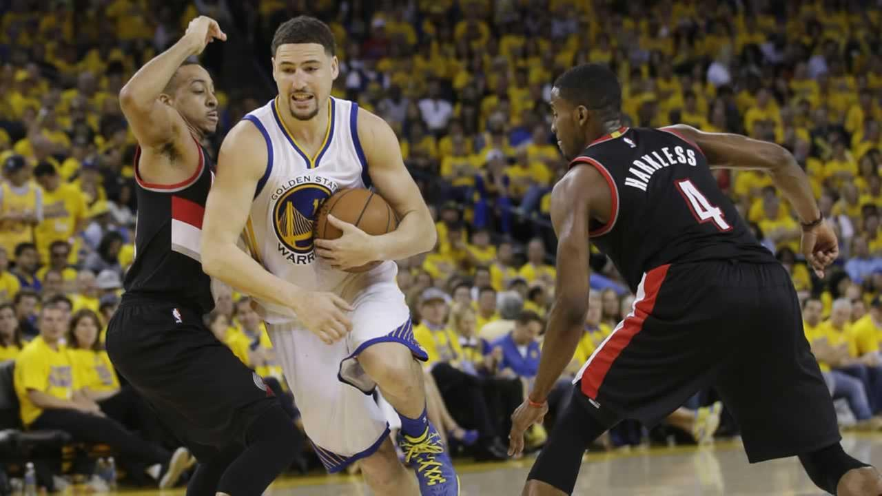 Warriors Klay Thompson dribbles between Portland Trail Blazers C.J. McCollum and Maurice Harkless on Sunday, May 1, 2016, in Oakland, Calif.