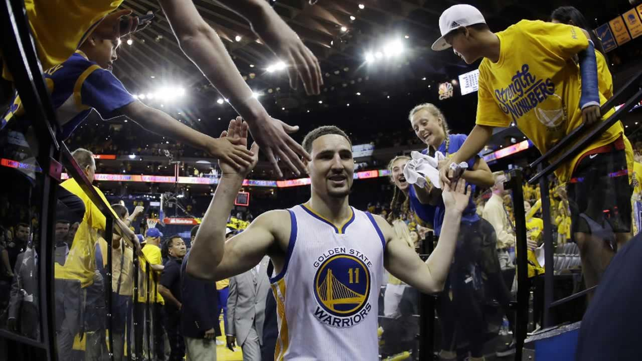 Golden State Warriors Klay Thompson (11) is high-fived by fans, Sunday, May 1, 2016, in Oakland, Calif.