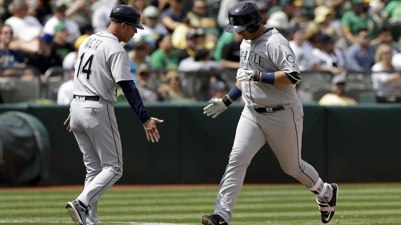 Mariners Dae-Ho Lee  is congratulated by third base coach Manny Acta after hitting a two run home during a game in Oakland, Calif. on May 4, 2016. (AP Photo/Ben Margot)