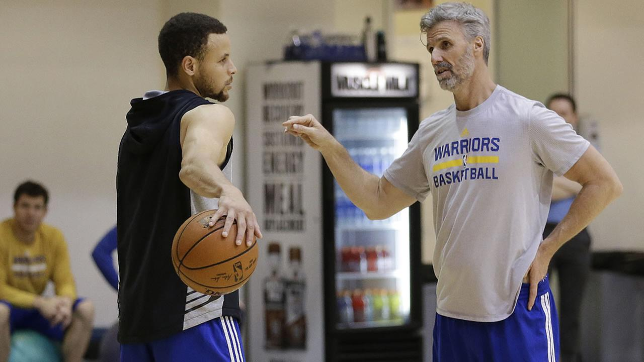 Golden State Warriors Stephen Curry, left, speaks with player development coach Bruce Fraser during NBA basketball practice on Thursday, May 5, 2016, in Oakland, Calif.