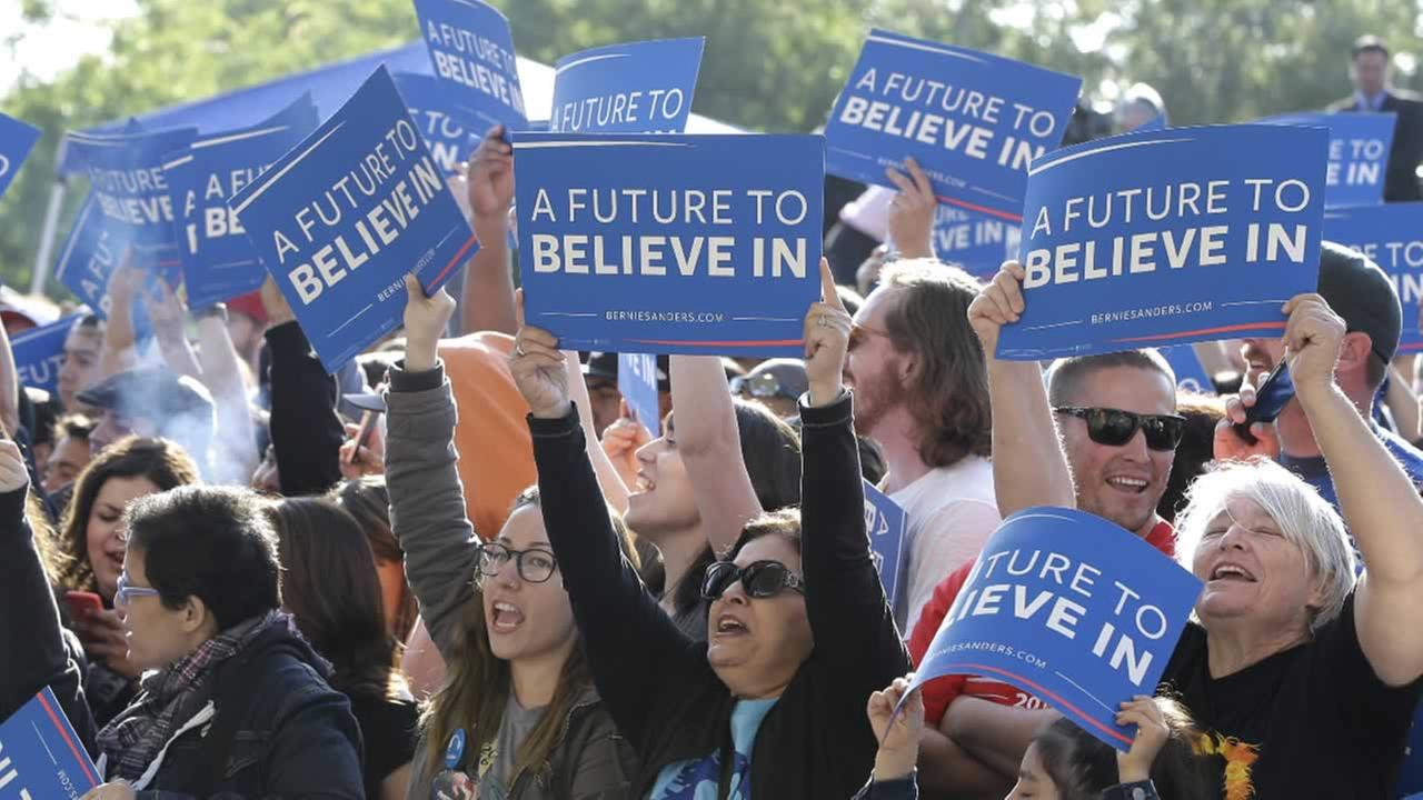 Supporters of Democratic presidential candidate, Sen. Bernie Sanders, I-Vt., wave signs before a campaign rally, Tuesday, May 10, 2016, in Stockton, Calif.