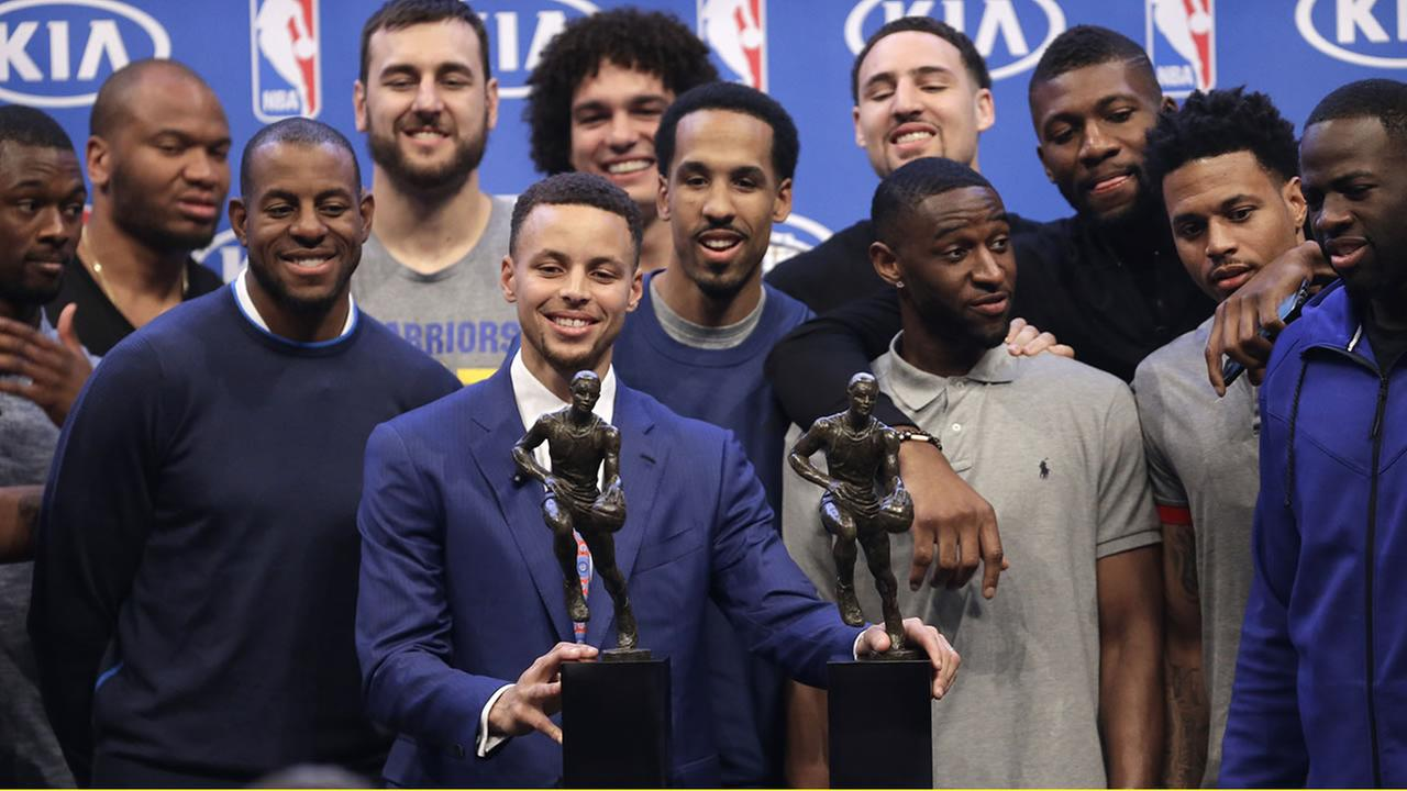 Golden State Warriors guard Stephen Curry, holding his NBA Most Valuable Player award trophies, takes a photo with his teammates on May 10, 2016, in Oakland, Calif. (AP Photo/Ben Margot)AP Photo/Ben Margot