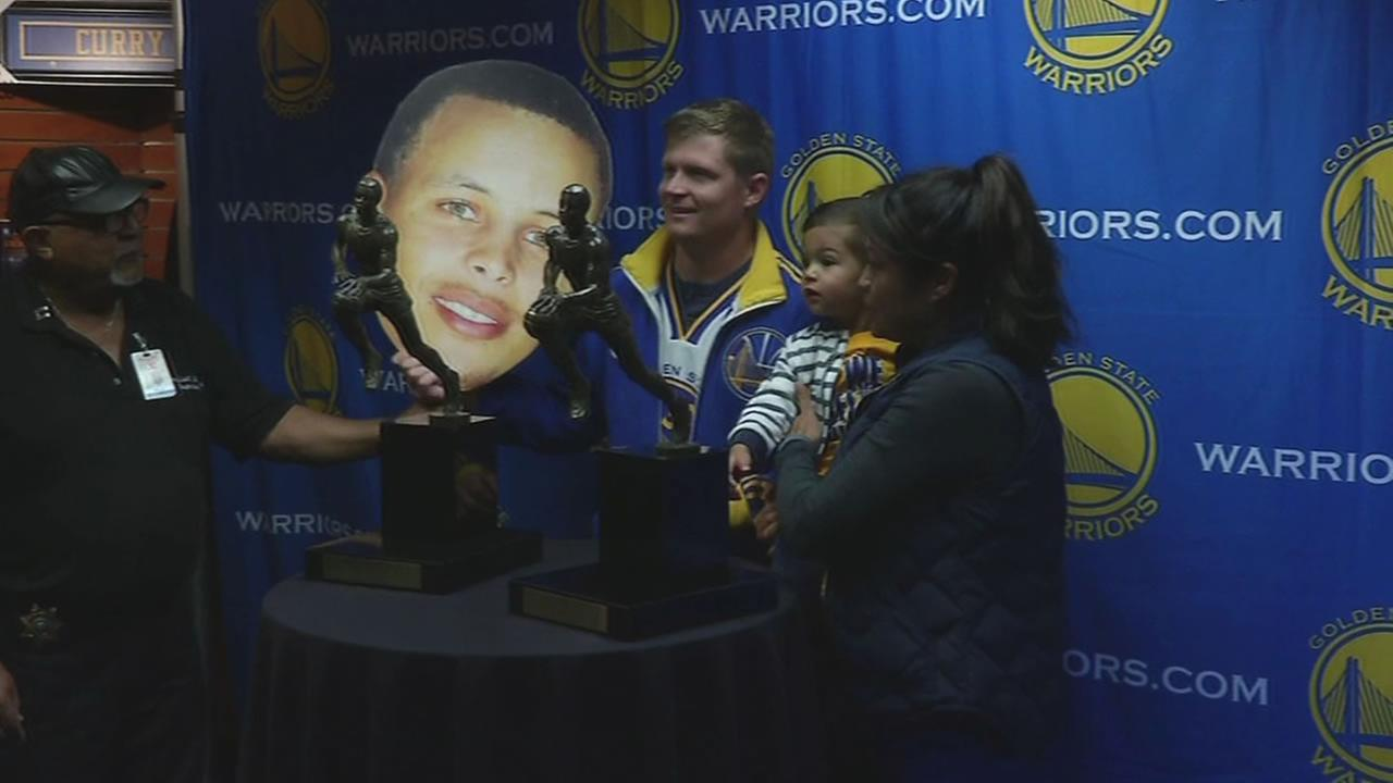 This image shows a Warriors fans taking photos with Steph Currys MVP trophies at the fan store at Oracle Arena.
