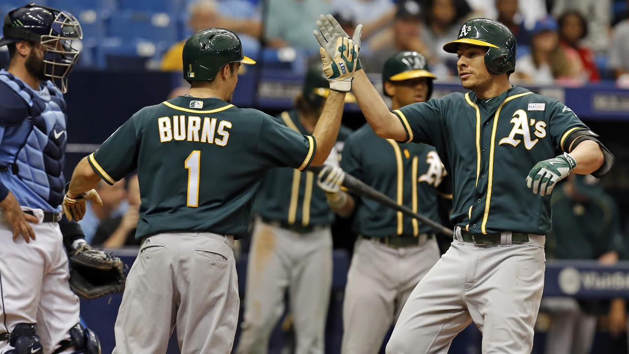 Oakland Athletics Danny Valencia, right, is congratulated by Billy Burns after his home run scored both of them during a game, Sunday, May 15, 2016, in St. Petersburg, Fla.