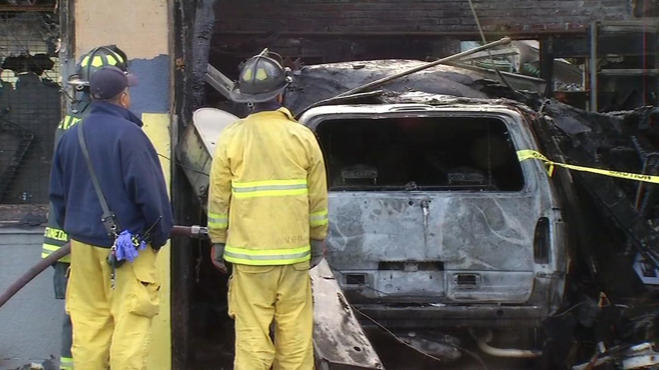 San Jose firefighters examine damage at auto repair shop, Monday, May 16, 2016.